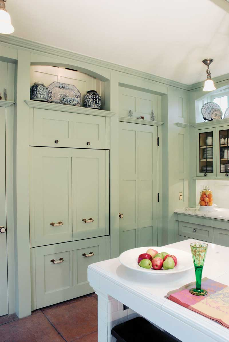 Concealed lighting casts a glow behind the arch and beneath cabinets.