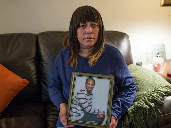 Carolyn Moses holds a photograph of her son, Jamil Moses, in her home in Northeast Philadelphia. Jamil was shot to death on February 8, 2011, after police boxed in the stolen car in which he was a passenger. (COLIN KERRIGAN / Philly.com)