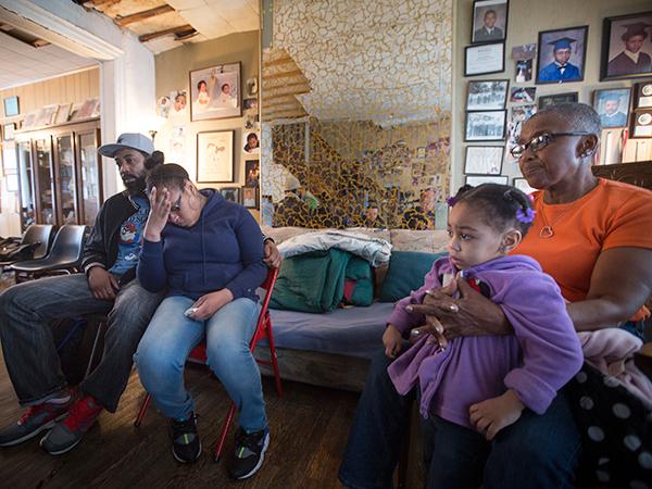 Troy Burroughs, cunhado, Shakira Wilson-Burroughs, irmã e Constance Wilson, avó, segurando a sobrinha, Sytira, do policial caído Robert Wilson, como eles falam sobre ele sábado, 7 de março de 2015. (DAVID SWANSON / fotógrafo de pessoal)