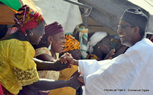 Nuhu Ribadu shakes hands with  supporters during a campaign visit to Borrong village in Adamawa