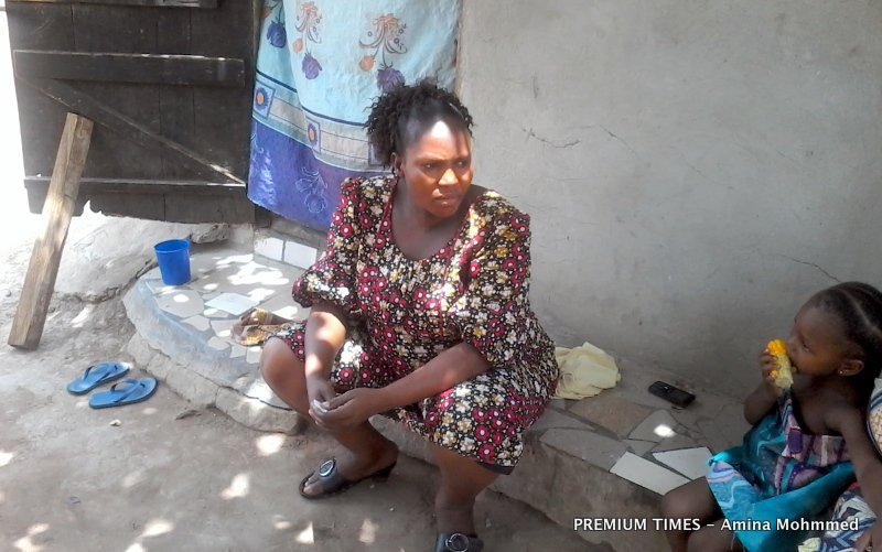 Mary Paul, pregnant with her seventh child, watches one of her children munch a stick of boiled corn for her breakfast