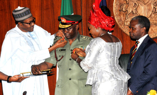 President Muhammadu Buhari (L)  Aided By Wife Of The Chief Of Defence Staff, Mrs Omobolanle In Decorating The Chief Of Defence Staff, Gen. Abayomi Gabriel Olonisakin,  At The Presidential Villa In Abuja On  Thursday (13/8/15) With Them Is  Vice-President Yemi Osinbajo. | NAN