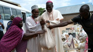 Bishop Mamza and the Secretary of the Islamic Council of Nigeria, Adamawa state chapter, Dauda Bello distributing grains to victims in St. Anne's Catholic Church, Michika, Adamawa