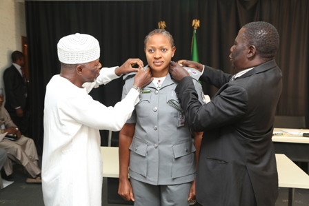 Decoration of DCG Grace Adeyemo by the CGC Col. Hameed Rtd being assisted by the Customs Assistant Legal Adviser