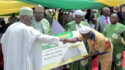 Gov. Abdulfatah Ahmed presenting cheque to a beneficiary of the SME schemes in Kwara state