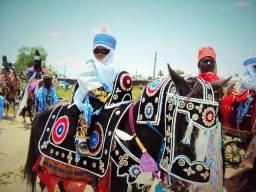 A young boy riding on a horse at the Bauchi Sallah Durbar