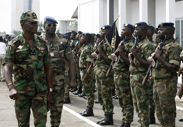 Ivorian army chief General Philippe Mangou (L) reviews his soldiers during a ceremony marking the start of the deployment of government forces in areas controlled by former rebels, at the army's headquarters in Abidjan May 5, 2009. A total of 4,000 government soldiers and an equal number of former rebels will be deployed across the country to provide security for the electoral process, army chief General Philippe Mangou said on Tuesday. Ivory Coast, the world's top cocoa producer, will hold its long-delayed presidential elections by December 6 at the latest, the West African country's U.N. ambassador said last week. REUTERS/Luc Gnago   (IVORY COAST POLITICS MILITARY ELECTIONS)