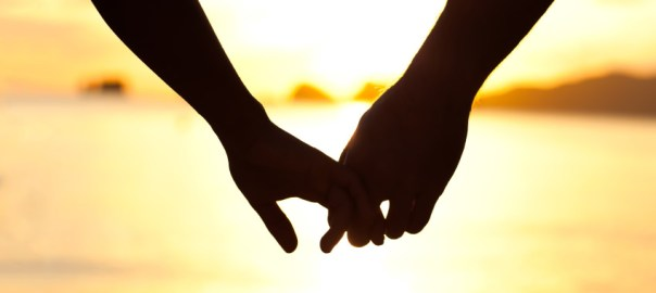 Couple holding hands used to illustrate a marriage