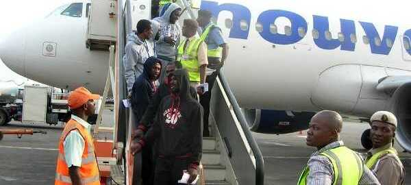 FILE PHOTO: Some of the 171 Nigerians who voluntarily returned from Libya before they disembarked form their aircraft on arrival at the Murtala Muhammed International Airport, Ikeja. {Photo; NAN]