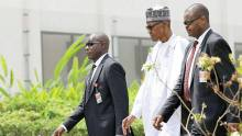 FILE PHOTO: President Muhammadu Buhari with his security detail heading to his office