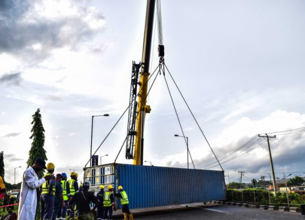 Men of Lagos State Emergency Management Agency (LASEMA) using a crane to lift off a falling trailer and container at an accident scene at 7up adjacent motorways bus stop, Outward Lagos-Ibadan Expressway in the early hours of Tuesday, May 23, 2017.