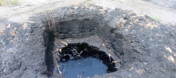 Puddled allegedly dug by Shell filled with spilled oil at at oil well inn K-Dere, Ogoni land