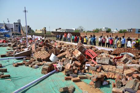 Indian people gather near the debris of a building where at least 24 people were killed when a wall collapsed at a wedding in the Bharatpur district of Rajasthan, India, 11 May 2017. An additional 30 people were also wounded, when the concrete wall fall on people taking shelter from a storm during the event.  EPA/VISHAL BHATNAGAR