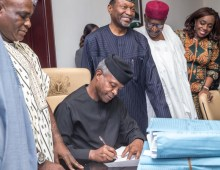Acting President Osinbajo signing the 2017 Budget