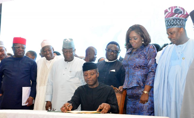 Acting President Yemi Osinbajo signing the Executive Order during the laaunch of Voluntary Assets and Income   Declaration Scheme (VAIDS) at the Presidential Villa, Abuja on Thursday (29/76/17) With him are: Minister of Finance, Mrs   Kemi Adeosun (2nd R) and State Governor 03592/25/6/2017/Callistus Ewelike/NAN