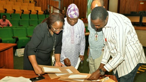Representatives of some of the firms that participated in the bids opening exercise with NNPC General Manager, Supply Chain Management, Sophia Mbakwe (first Left), examining documents for the selection of firms to provide security services at the NNPC's depots and pump stations across the country.