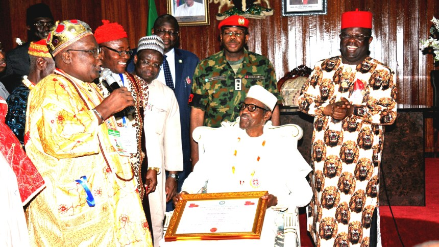 President Muhammadu Buhari (sitting) being confered with Enyi Oma 1 of Ebonyi by the Chairman, Ebonyi State Council of Tradtional Rulers, Eze Charles Mkpuma (l) during President's State visit to Abakaliki, Ebonyi State on Tuesday (14/11/17) with them is Gov Dave Umahi of Ebonyi State (r) 06096/14/11/2017/Callistus Ewelike/NAN