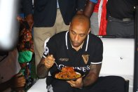 Arsenal legend, Thierry Henry, eating Nigerian jollof rice.