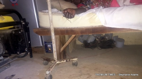 A patient laying on a bed placed on a wooden bench in PHC Gudi