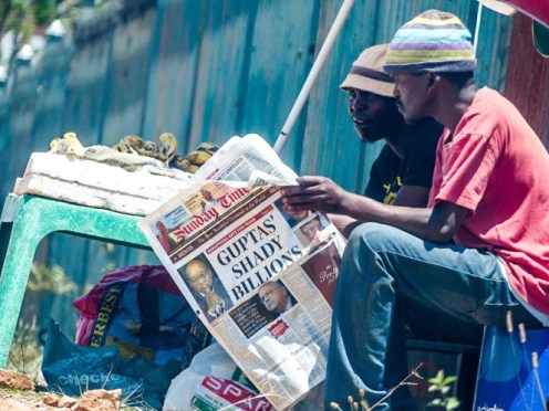 Two South African men read a newspaper detailing a financial scandal involving the Gupta family, October 2016. Photo: CC BY-NC-ND 2.0: Skatkat / Flickr.