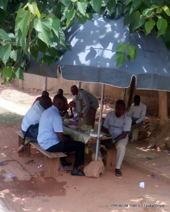Nigerians eating at a food stand in Wuse.