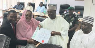 Chairman of INEC, Mahmood Yakubu presenting the certificates. [Photo credit: Official Twitter account of INEC]