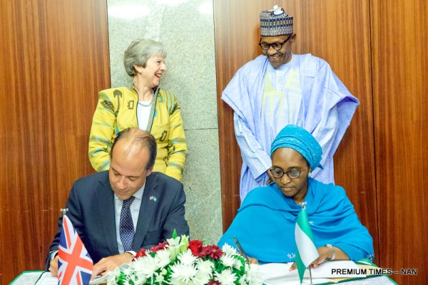 President Muhammadu Buhari (standing R) and British Prime Minister Theresa May witnessing as Nigerian National Security Adviser, retired Babagana Monguno (R) and British Deputy National Security Adviser, Christian Turner sign Bilateral agreement on Defence and Security Partnership during the visit of the British Prime Minister to the Presidential Villa in Abuja on Wednesday (29/8/18)