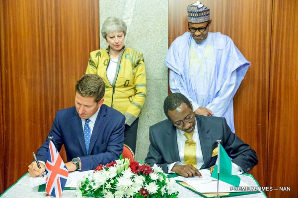 President Muhammadu Buhari (standing R) and British Prime Minister Theresa May witnessing as Nigeria Minister of State for Budget and National Planning, Hajia Zainab Ahmed and British Minister of State for Trade Policy, George Hollingbery sign a Bilateral on Nigeria Trade Development during the visit of the British Prime Minister Minister to the Presidential Villa in Abuja on Wednesday (29/8/18)