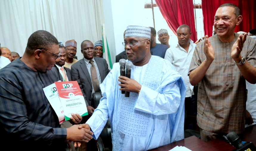 Former Vice President of Nigeria and frontline presidential aspirant of the Peoples Democratic Party (PDP), Atiku Abubakar submitting his Nomination and Expression of Interest forms to the National Organising Secretary of the PDP, Col Austin Akobundu (rtd), while Senator Ben Bruce cheers on at the party's national secretariat in Abuja on Thursday.