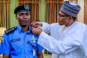 Acting IGP Mohammed Adamu being decorated by President Muhammadu Buhari