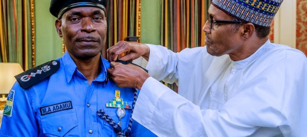 Acting IGP Mohammed Adamu being decorated by President Muhammadu Buhari