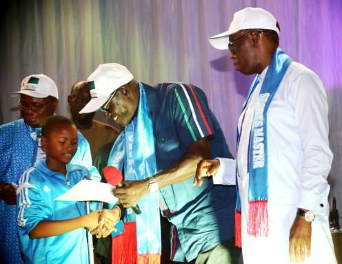 Delta State Governor, Senator Ifeanyi Okowa (right), watching as the State PDP Chaiurman, Barr. Kingsley Esiso, presents certificate and Cheque to a Gold medalist, Precious Okoafor, at the Reception/Award of Athletes and Officials to the 4th National Youth Games 2018 and the 19th National Sports Festival, Abuja, in Asaba. PIX: BRIPIN ENARUSAI