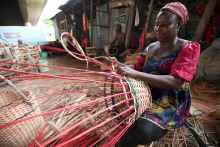 A woman weaves cane sticks to produce baskets in the Maryland community in Ikeja, Lagos, Nigeria [Photo: EPA - Ahmed Jallanzo]