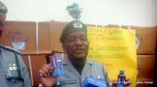 Comptroller Aliyu Mohammed displaying a bottle of the seized codeine syrup (Photo credit: Kingsley Adeniyi)