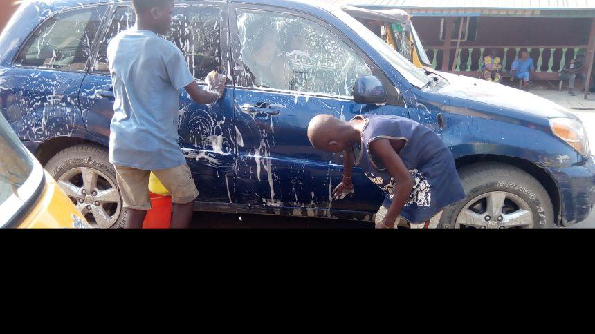 Underage kids washing cars at Mile 10, Ojo, LAgos.