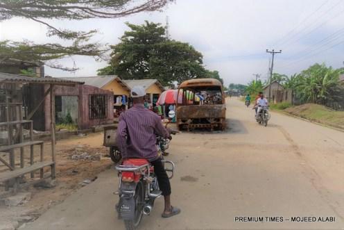 Nuka on motorcycle near burnt HYPREP bus