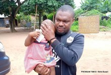Mr Gwamnishu Harrison, the head of Behind Bars Rights Foundation, holding the two-year-old rape victim