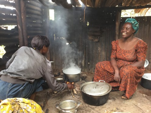Kanyere Vwatire (right), an Ebola survivor, cooks lunch for her family days after being discharged from the Katwa Ebola Treatment Centre. (Credit: WHO/Y. Maiga)