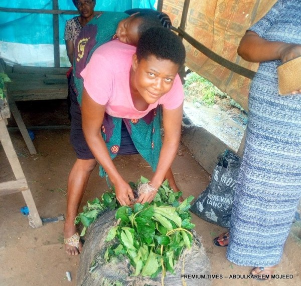 Nelly Ikpe wrapping bunches of Ugu bought.