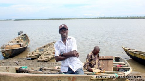 Nsopikpo Afia sits on his canoe as helpless after oil spills destroyed his fishing nets