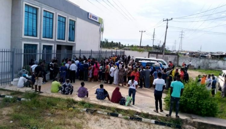 Nigerians queuing up to access the bank.