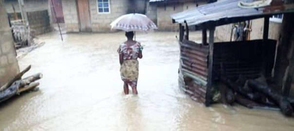 A woman wades through the flood to reach her house in Amasiri, Afikpo north local government area.
