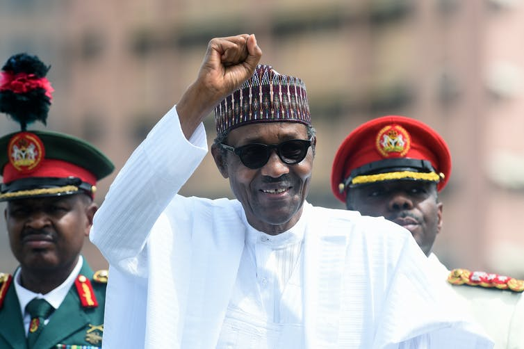 President Muhammadu Buhari raises his fist during an inspection of honour guards on parade to mark Democracy Day in Abuja, on June 12, 2019. Pius Utomi Ekpei/AFP via Getty Images