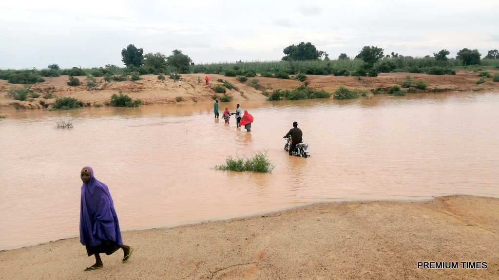 Community members struggling to cross to the other sides of the village