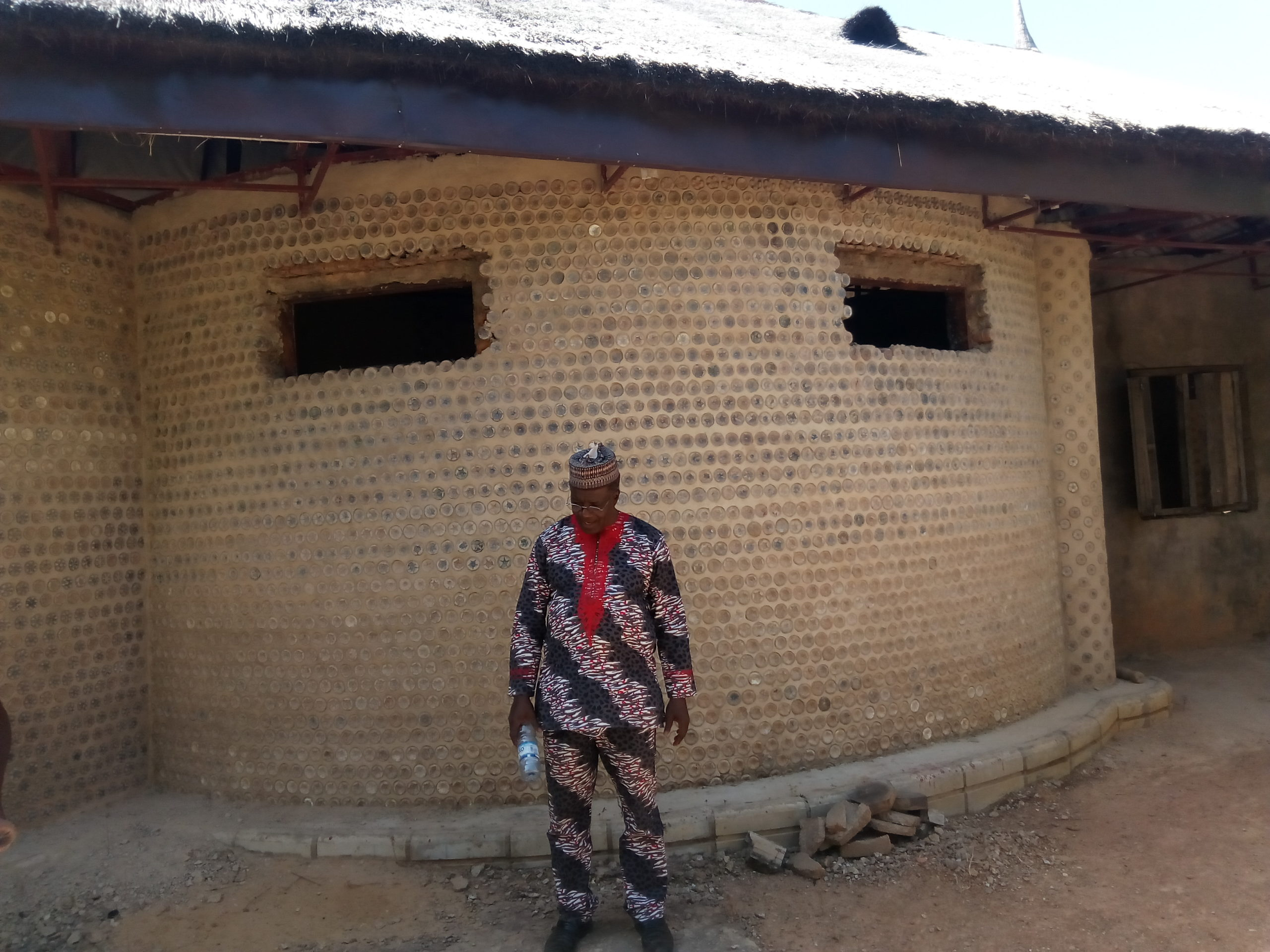 Yahaya Ahmed standing outside his newly built plastic house