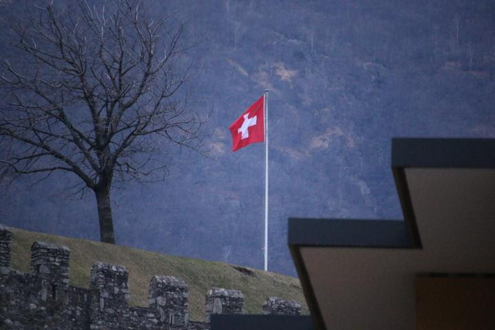 A Swiss Flag on a hill beneath a mountain in Bellinzona, Switzerland. New Narratives/James Harding Giahyue