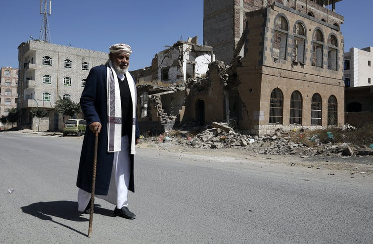 A man with a walking stick walks past a bombed building in Sana'a, Yemen, February 2021.Sana'a, Yemen, after a Saudi airstrike. EPA-EFE/Yahya Arhab