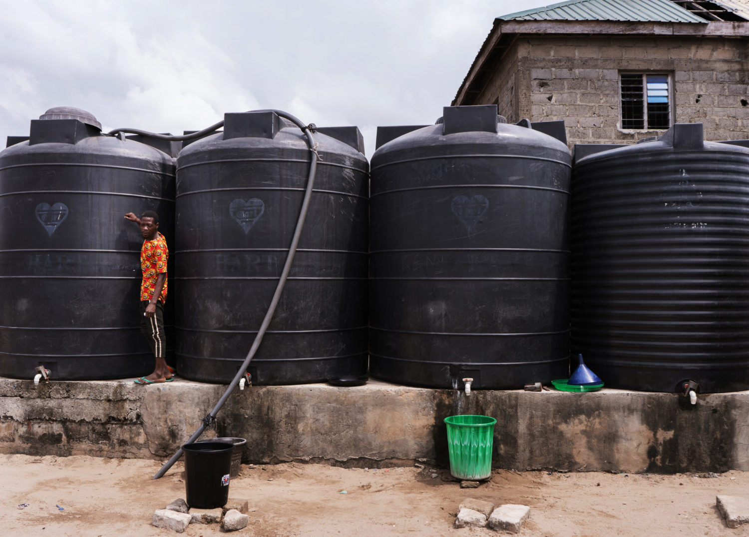 A worker checks the level of the water in tanks owned by waterpreneurs, who ferry it to Sagbo Kodji in specially built boats. [PHOTO CREDIT: Nengi Nelson]