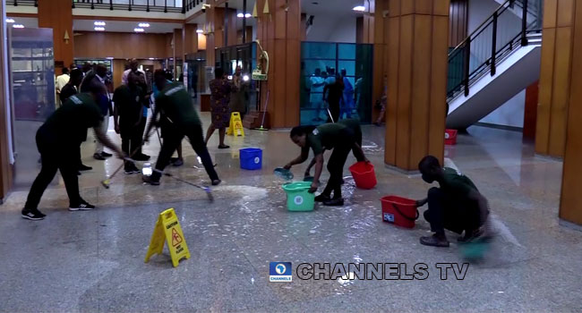 Janitors mopping up wet floor at the National Assembly [PHOTO: Channels]