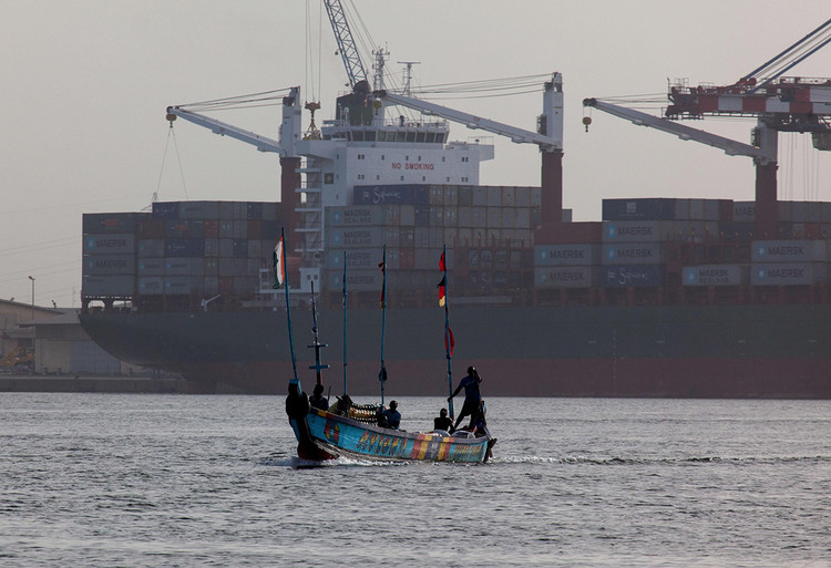A boat seen in the Lagoon of Abidjan as a container ship is seen docked in the background. [Credit: Roux Olivier/Alamy]